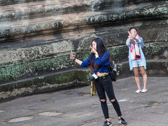 Two ladies taking selfies in a courtyard at Angkor Watt in Cambodia