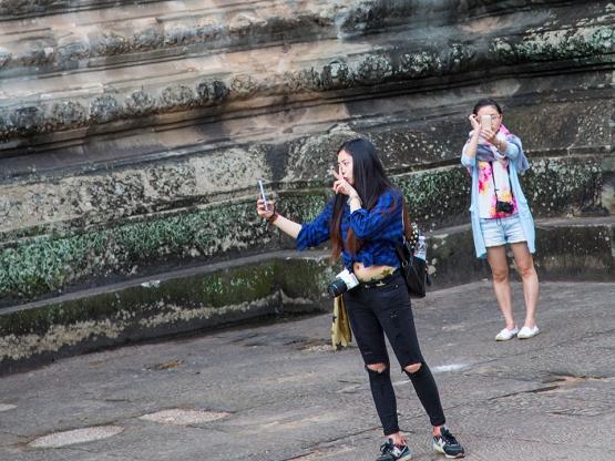 Two ladies taking selfies in a courtyard at Angkor Watt in Cambodia