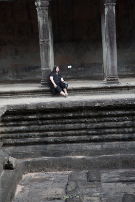 Tourists perched on a wall taking selfies at Angkor Watt in Cambodia