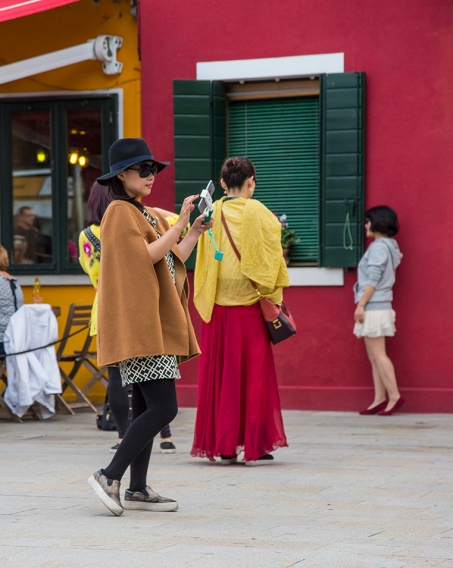 Several young ladies take selfies on the streets of Burano, Italy
